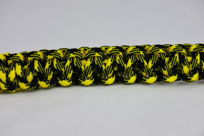 black and yellow camouflage paracord bracelet across the middle of a white background