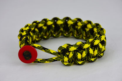 black and yellow camouflage paracord bracelet unity band with red button, picture of a black and yellow camouflage paracord bracelet unity band with red button fastener in the front on a white background