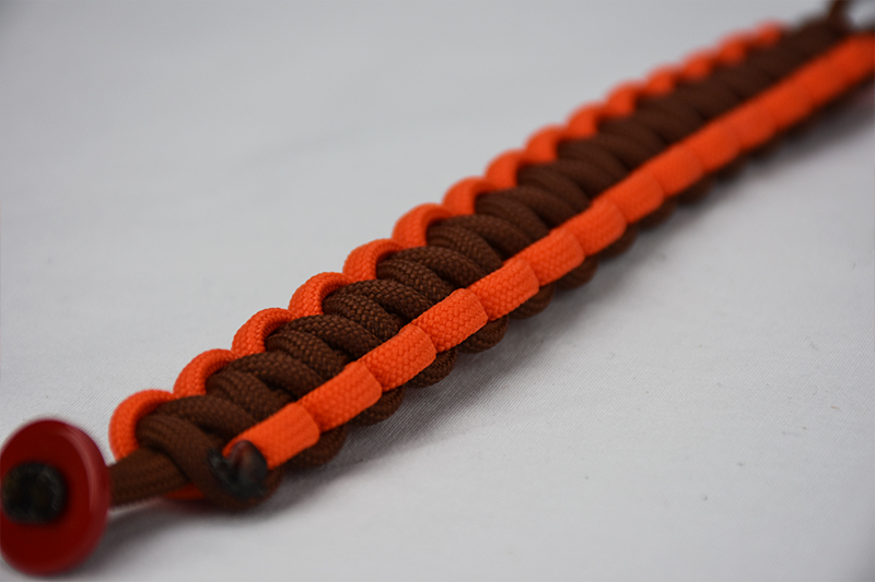brown orange and brown paracord bracelet unity band with red button in the corner, brown orange and brown paracord bracelet with red button fastener in the front corner on a white background