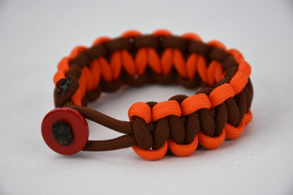 brown orange and brown paracord bracelet unity band with red button in the front, picture of a brown orange and brown paracord bracelet unity band with red button fastener in the front on a white background