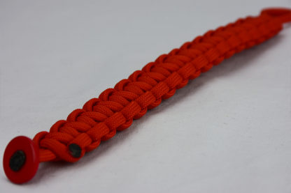 burnt orange paracord bracelet unity band with red button corner, picture of a burnt orange paracord bracelet with red button fastener on a white background