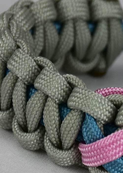 custom support ribbon paracord bracelet, picture of a grey and light blue paracord bracelet with a light blue and soft pink support ribbon