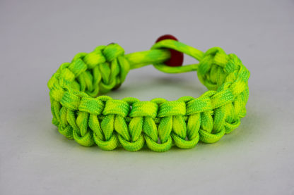 dayglow camouflage paracord bracelet unity band with red button in the back, picture of a dayglow camouflage paracord bracelet with red button fastener in the back on a white background