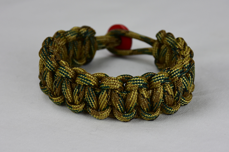 multicam camouflage paracord bracelet unity band with red button in back, picture of a multicam camouflage paracord bracelet unity band with red button fastener in the back on a white background