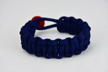 navy blue paracord bracelet unity band with red button, picture of a navy blue paracord bracelet unity band with red button fastener in the back on a white background