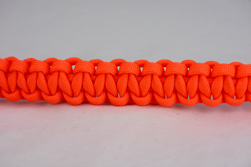 neon orange paracord bracelet across the center of a white background