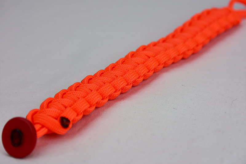 neon orange paracord bracelet unity band with red button, picture of a neon orange paracord bracelet with red button fastener in the corner