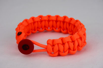 neon orange paracord bracelet unity band with red button, picture of a neon orange paracord bracelet unity band with red button in the front on a white background