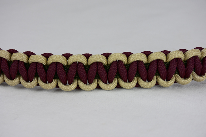 od green desert sand and burgundy paracord bracelet across the center of a white background