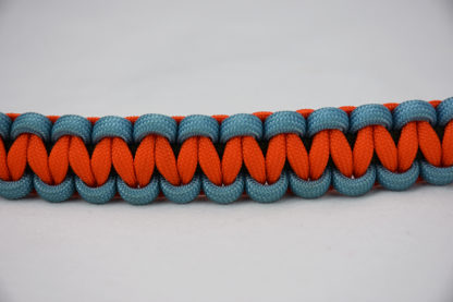 od green light blue and orange paracord bracelet going across the middle of a white background