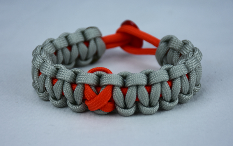 orange and grey leukemia support paracord bracelet with orange ribbon and red button, picture of a orange and grey paracord bracelet unity band with a orange ribbon in the center and red button fastener, leukemia support