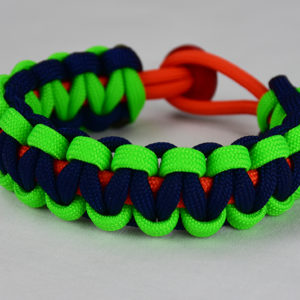 orange neon green and navy blue paracord bracelet with red button back, picture of an orange neon green and navy blue paracord bracelet with red button fastener in the back on a white background