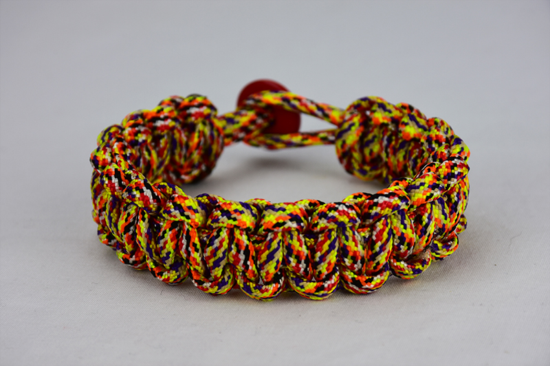 overkill camouflage paracord bracelet unity band with red button in the back, picture of an overkill camouflage paracord bracelet unity band with red button fastener in the back