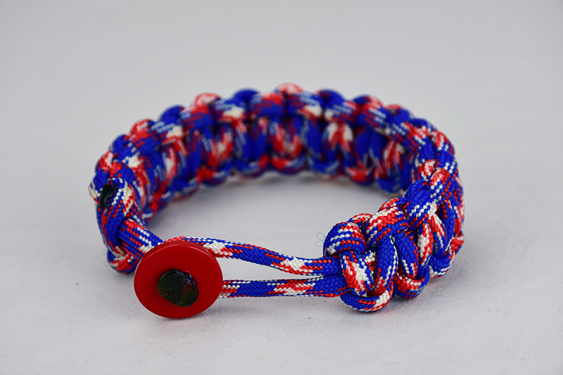 patriotic camouflage paracord bracelet with red button front, picture of a patriotic camouflage paracord bracelet unity band with red button fastener in the front, red white and blue camouflage for patriotism