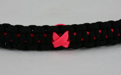 pink and black breast cancer support paracord bracelet with pink ribbon in the center
