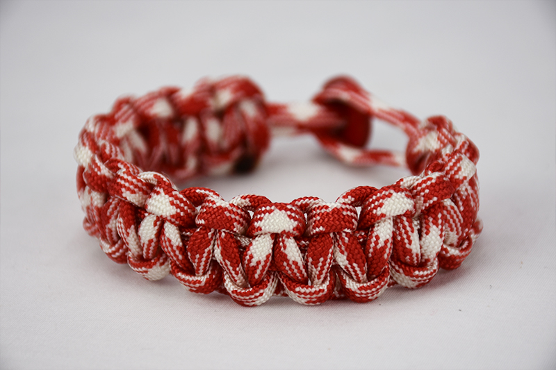 red and white camouflage paracord bracelet with red button in the back, picture of a red and white camouflage paracord bracelet unity band with red button fastener in the back on a white background