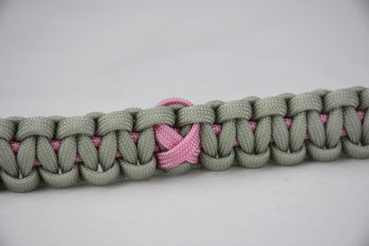 soft pink and grey breast cancer support paracord bracelet with a pink ribbon in the center, picture of a soft pink and grey breast cancer support paracord bracelet unity band with a pink ribbon in the center of the band
