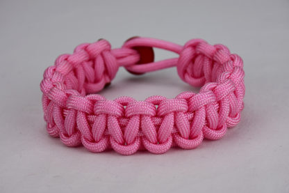 soft pink paracord bracelet unity band with red button, picture of a soft pink paracord bracelet with red button fastener in the back on a white background