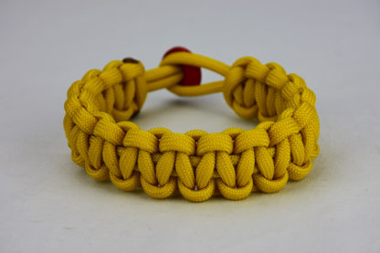 yellow paracord bracelet unity band with red button in back, picture of a yellow paracord bracelet unity band with red button fastener in the back on a white background