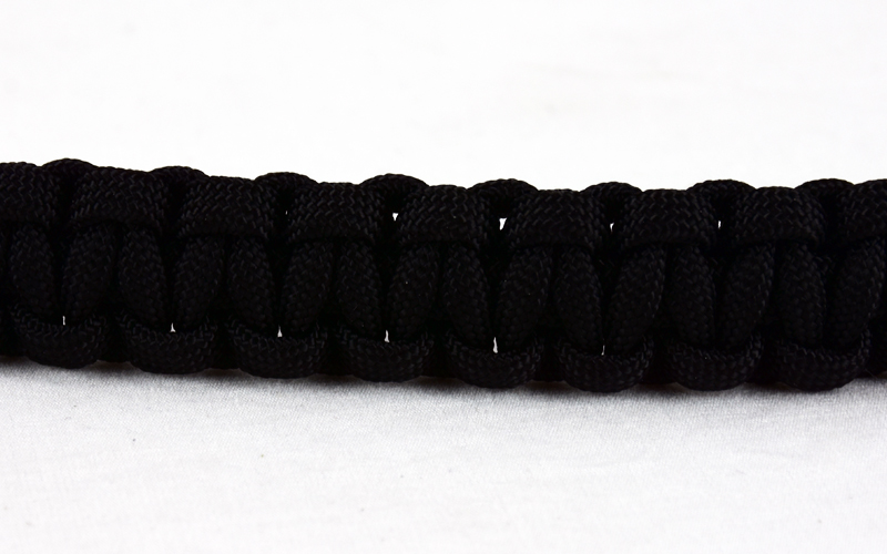 black paracord bracelet across a white background