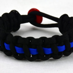 black paracord bracelet with blue line and a red button fastener in the back