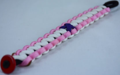 black soft pink and white alzheimers support paracord bracelet with red button fastener in the corner and purple ribbon